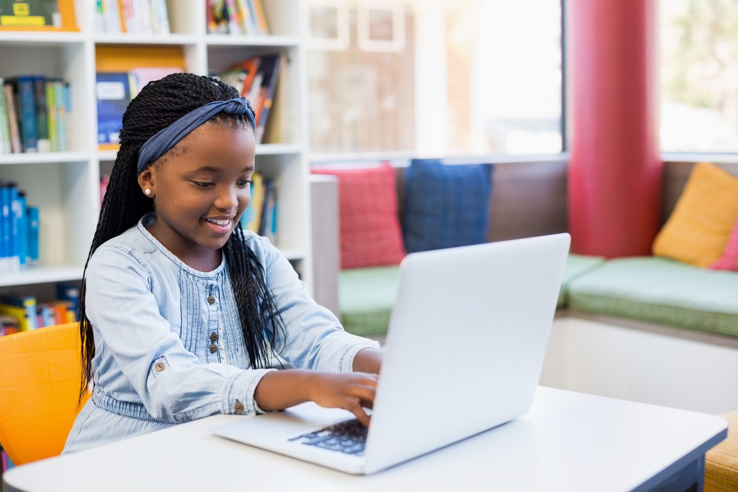 Schoolgirl,Using,Laptop,In,Library,At,School